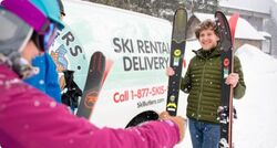 Man delivering skis to a woman